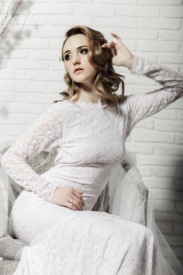 Piękna dziewczyna z blondynem w jaskrawym izbowym obsiadaniu na leżance Panna młoda w piękny długi smokingowy siedzący samotnym zdjęcie stock