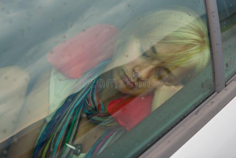 Piękna dziewczyna z blondynka włosy bierze drzemkę w samochodzie na deszczowym dniu zdjęcie stock