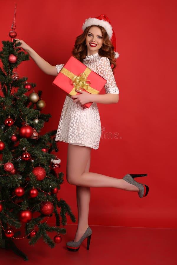 Piękna dziewczyna z ciemnym włosy w eleganckiej sukni z dużą Bożenarodzeniową teraźniejszością zdjęcia stock