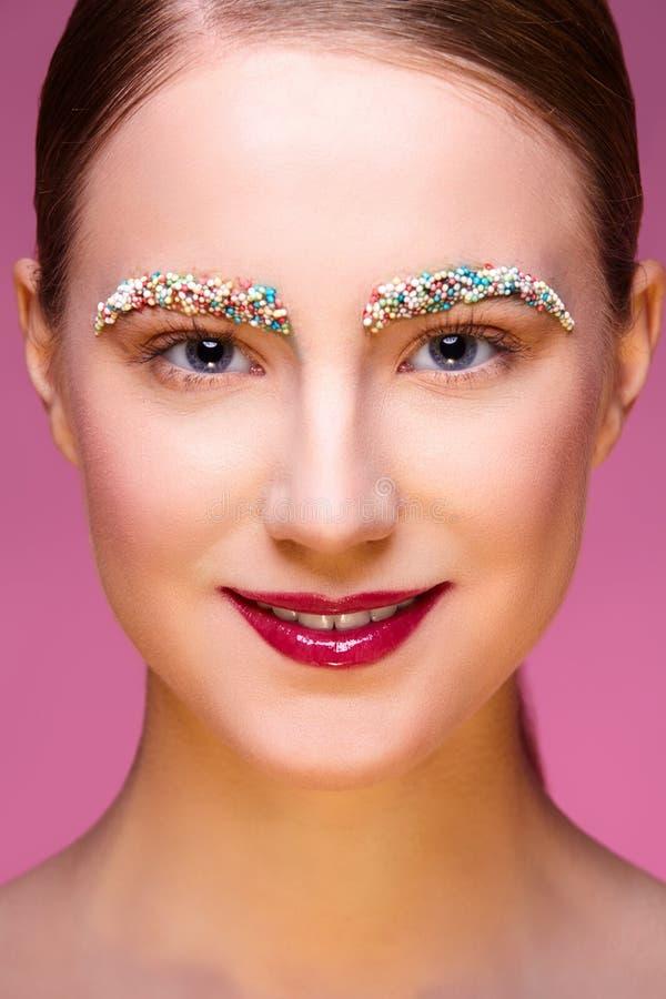 Piękna dziewczyna z cukierkami na różowym backgroound obrazy royalty free