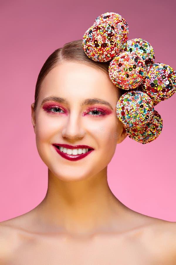 Piękna dziewczyna z cukierkami na różowym backgroound zdjęcia royalty free
