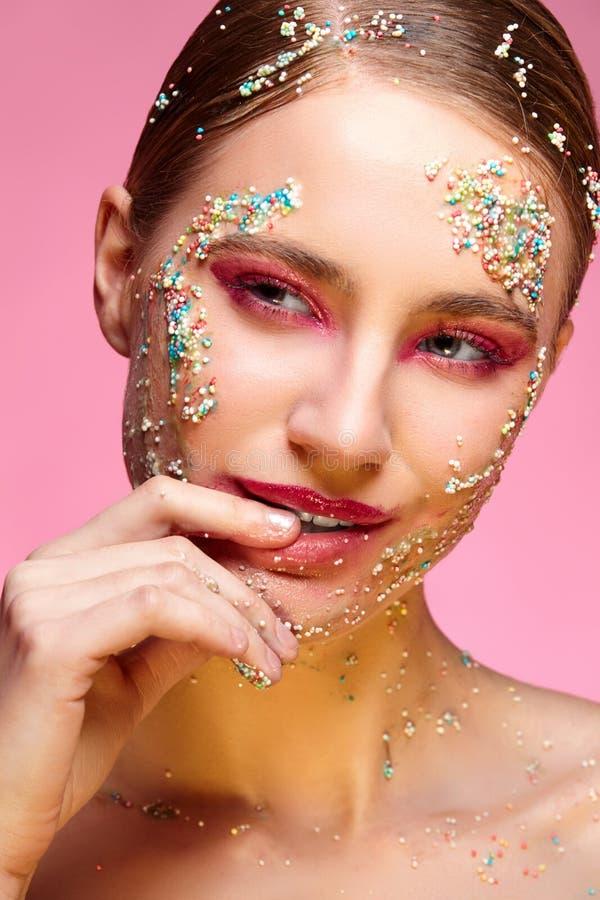 Piękna dziewczyna z cukierkami na różowym backgroound zdjęcia stock