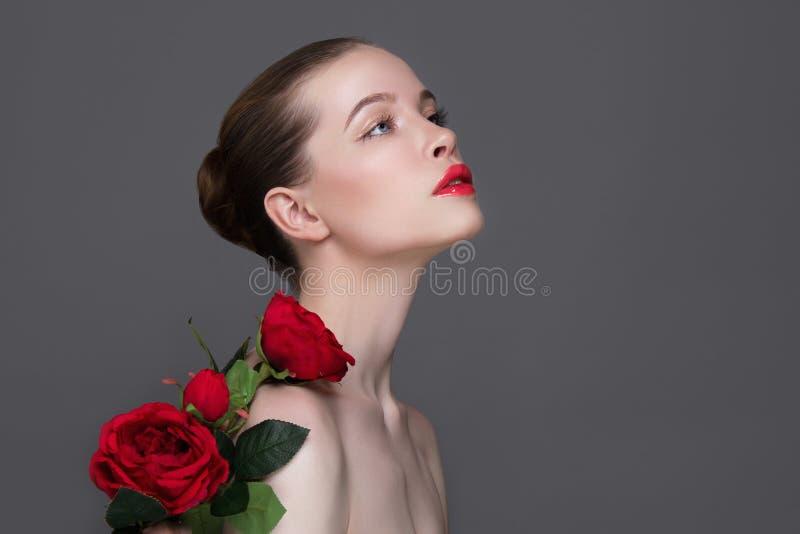 Piękna dziewczyna z czerwonych róż kwiatem obraz stock