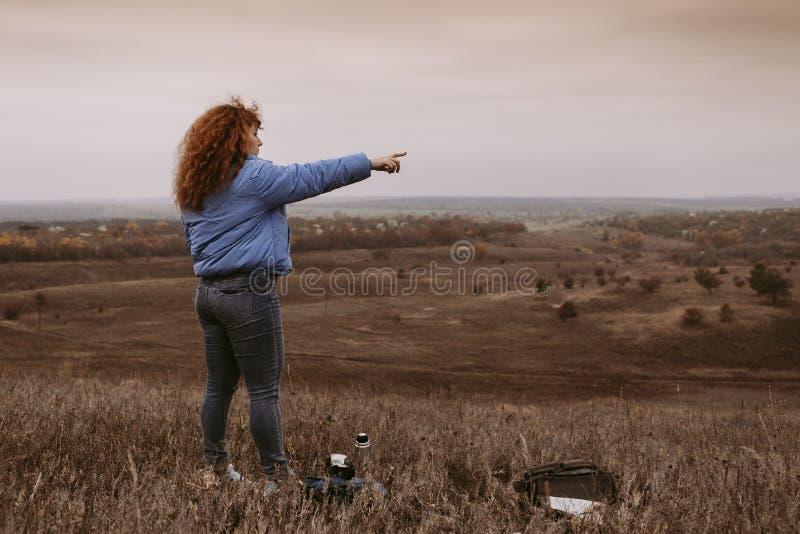 Piękna dziewczyna z czerwonym włosy podróżuje w, pije termos herbaty, podziwia scenerię, i przestronnych polach i łąkach zdjęcia stock