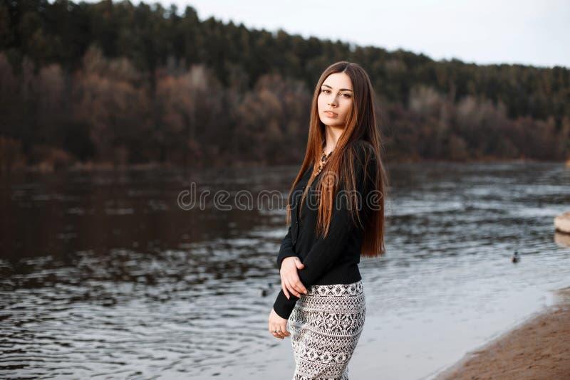 Piękna dziewczyna z długie włosy pozycją blisko rzeki na pogodnym zdjęcia stock