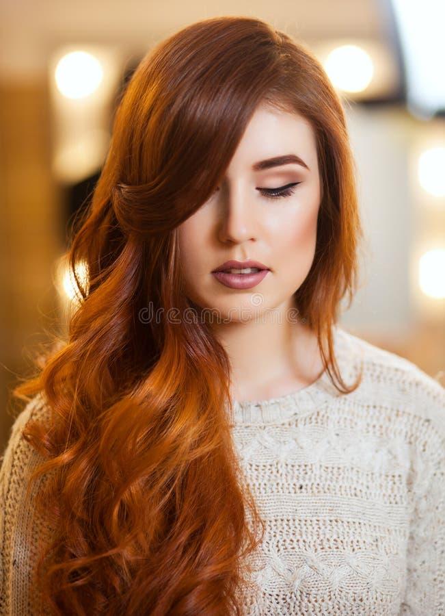 Piękna dziewczyna z długim, kędzierzawym czerwonym włosy w piękno salonie, obrazy stock
