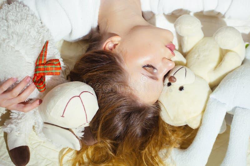 Piękna dziewczyna z kędzierzawego włosy dosypianiem w łóżku Ładna młodej kobiety przytulenia zabawka w sen słodki sen obrazy royalty free