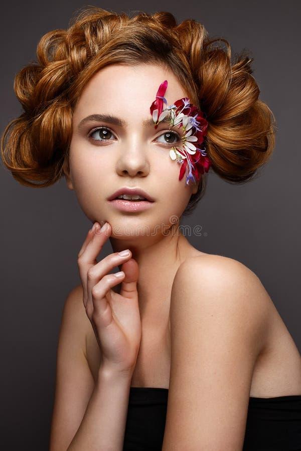 Piękna dziewczyna z kreatywnie makijażem z kwiecistymi aplikacjami Model w stylu romantycznego z kwiatów płatkami wokoło jej oczu fotografia royalty free