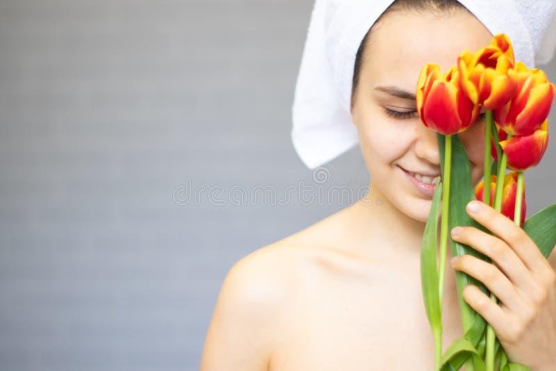 Piękna dziewczyna z kwiatów tulipanami w rękach na lekkim tle zdjęcia stock