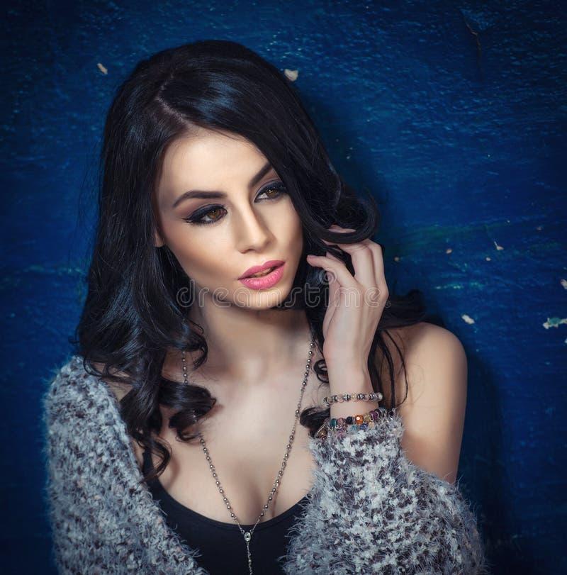 Piękna dziewczyna z makeup pozuje, stara ściana z strugać błękitną farbę na tle Ładna brunetka z puszystym pulowerem zdjęcie stock