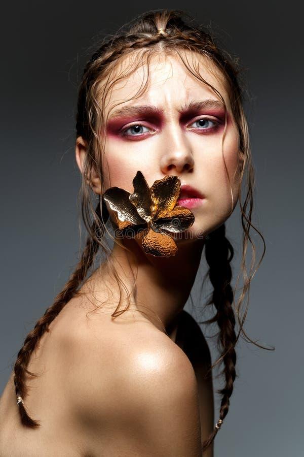 Piękna dziewczyna z nowożytnymi warkoczami i metal kwitniemy w usta obrazy royalty free