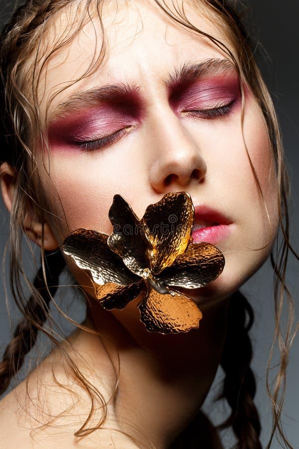 Piękna dziewczyna z nowożytnymi warkoczami i metal kwitniemy w usta zdjęcie stock