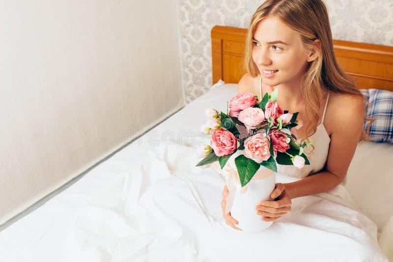 Piękna dziewczyna z peonią kwitnie obsiadanie na łóżku Ona właśnie w obraz stock