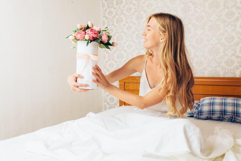 Piękna dziewczyna z peonią kwitnie obsiadanie na łóżku Ona właśnie w fotografia stock