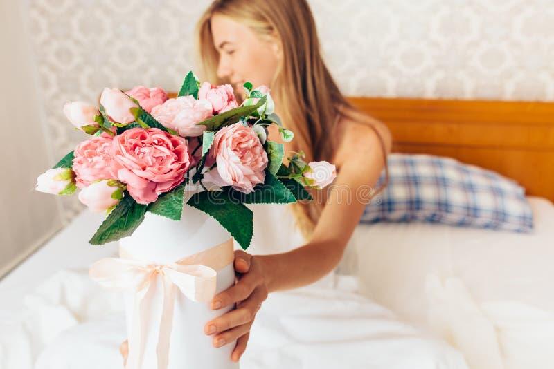 Piękna dziewczyna z peonią kwitnie obsiadanie na łóżku Ona właśnie w obrazy stock