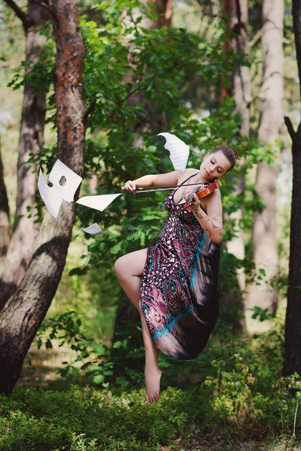 Piękna dziewczyna z skrzypce w długiej sukni unosi się wśród drzew zdjęcia royalty free