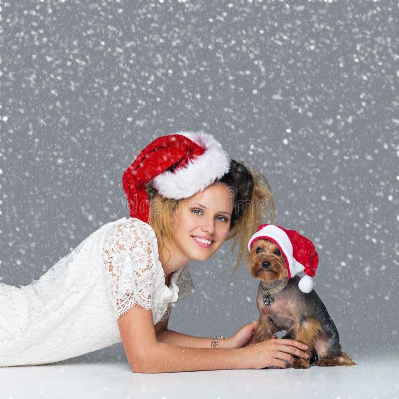 Piękna dziewczyna z yorkie psem w Santa nakrętce obrazy royalty free