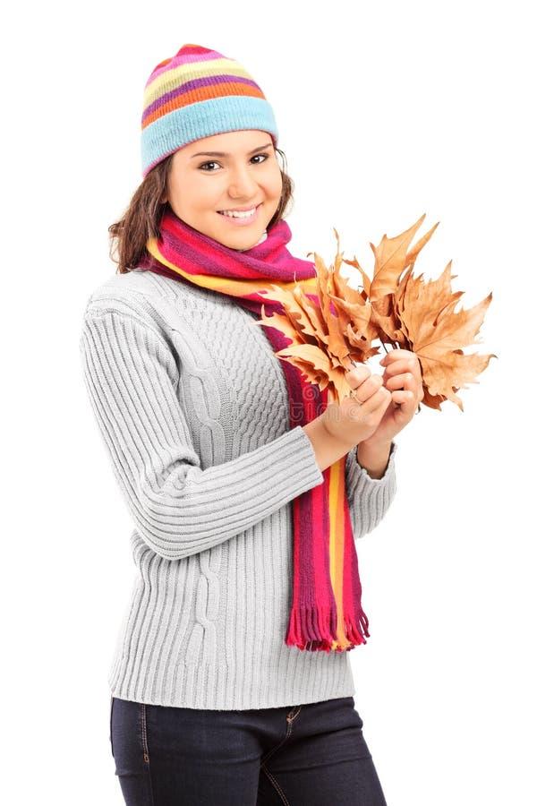 Piękna dziewczyna z zimy kapeluszowego mienia suchymi liśćmi obraz royalty free