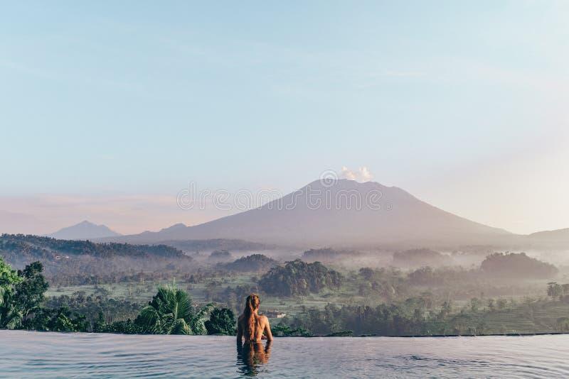 Piękna dziewczyna zostaje blisko pływackiego basenu z fantastycznym wulkanem obrazy stock