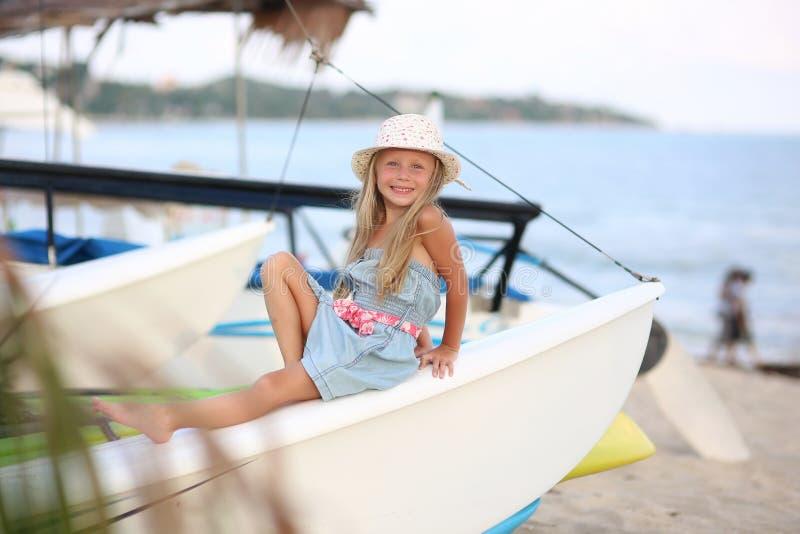 Piękna dziewczynka cieszy się luksusową wycieczką jachtową na wakacje letnie, słoneczny wiatr uśmiecha się patrząc na zew fotografia royalty free