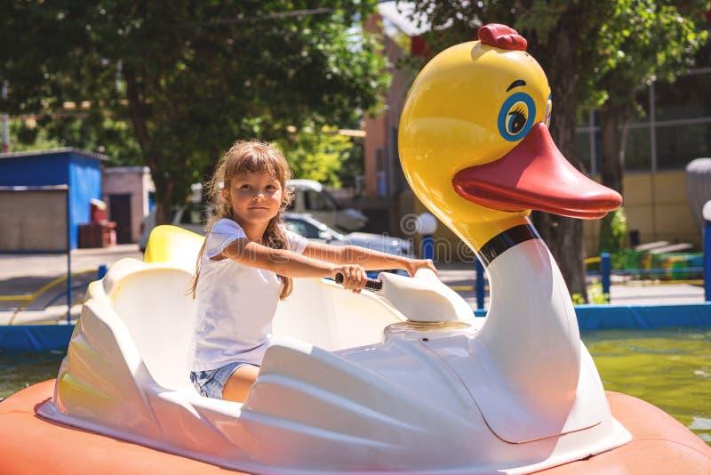 Piękna dziewczynka jedzie wodnego przyciąganie w lato parku tematycznym zdjęcie royalty free