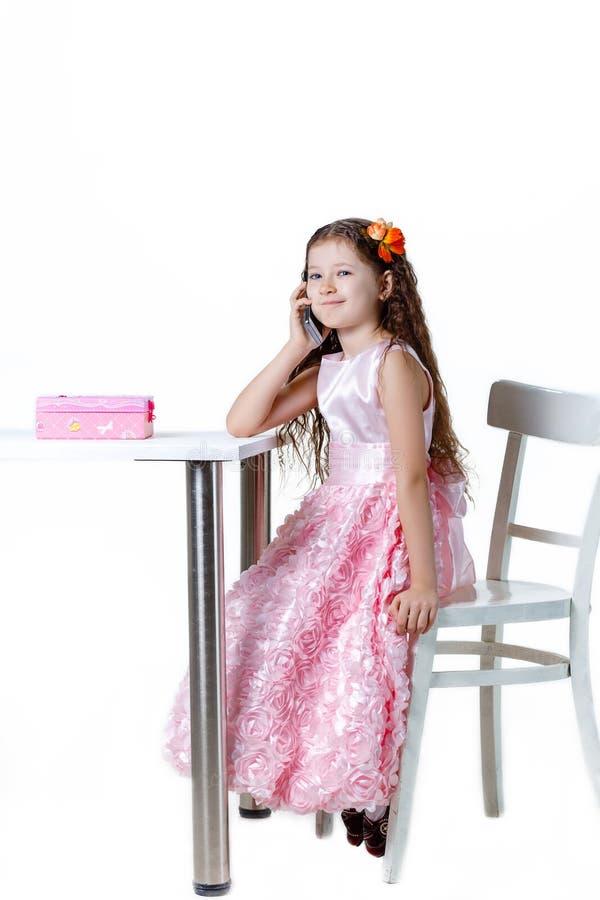 Piękna dziewczynka opowiada na telefonie w sukni odizolowywającej na białym tle fotografia royalty free