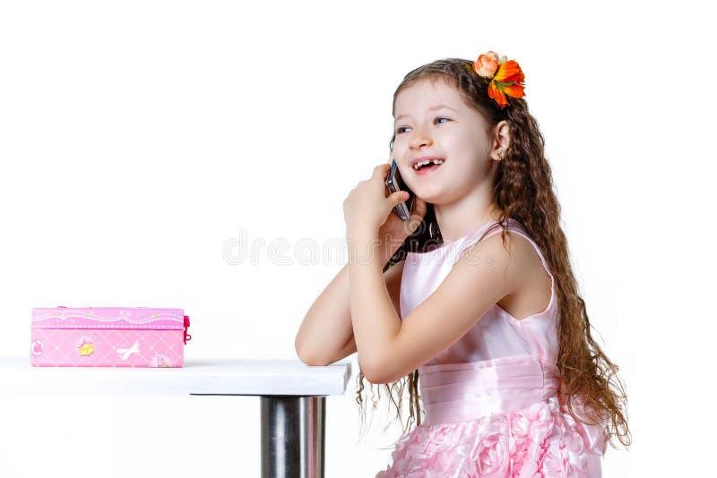 Piękna dziewczynka opowiada na telefonie w sukni odizolowywającej na białym tle zdjęcia stock