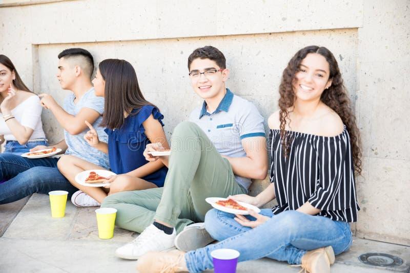 Piękna dziewczyny łasowania pizza z przyjaciółmi outdoors obrazy royalty free