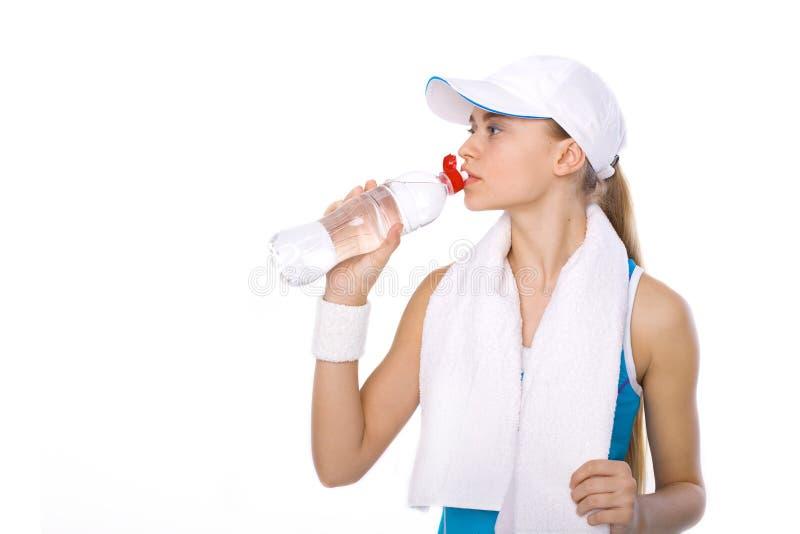 Piękna dziewczyny atleta z bidonem na białym tle obrazy royalty free
