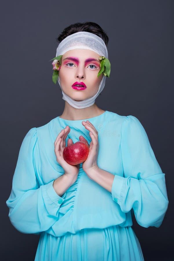 Piękna dziewczyny brunetki dziewczyna w błękitnej mody sukni z jaskrawym romantycznym makijażem, kwiaty na ona kierownicza i jabł zdjęcie royalty free