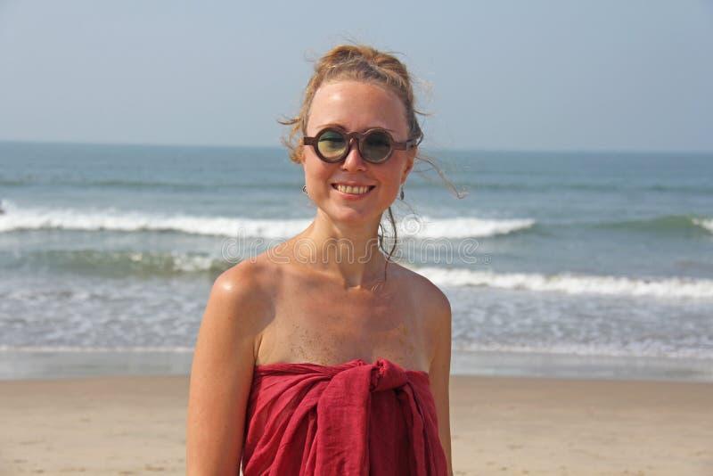 Piękna dziewczyny pokraka w czerwonym blondynie na backg i sukni, zdjęcia stock