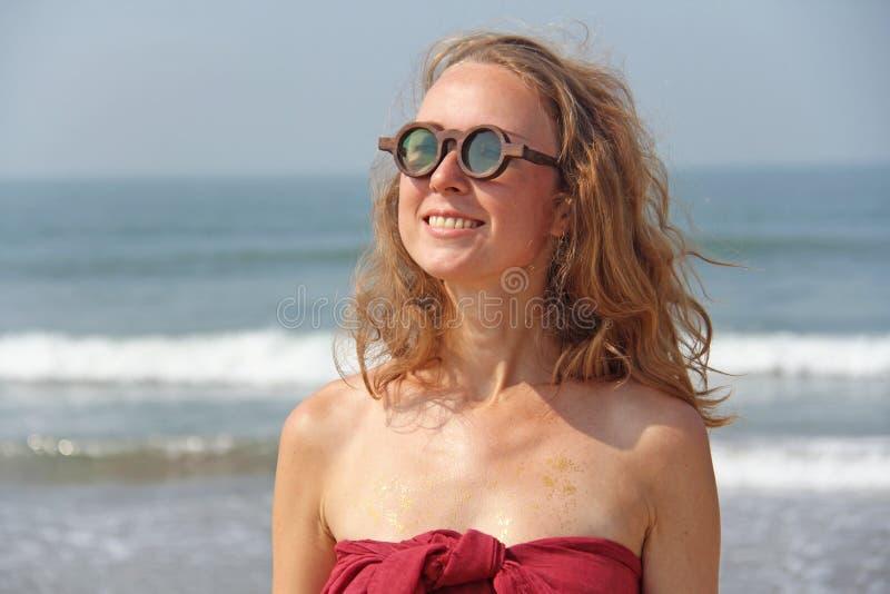 Piękna dziewczyny pokraka w czerwonym blondynie na backg i sukni, obraz royalty free