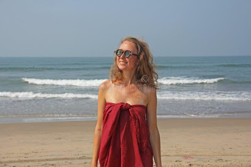 Piękna dziewczyny pokraka w czerwonym blondynie na backg i sukni, fotografia royalty free