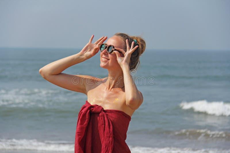 Piękna dziewczyny pokraka w czerwonym blondynie na tle morze i sukni, Lato dziewczyna w round drewnianych szkłach niezwykły zdjęcia royalty free