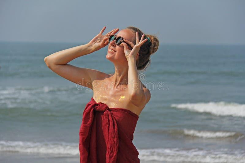 Piękna dziewczyny pokraka w czerwonym blondynie na tle morze i sukni, Lato dziewczyna w round drewnianych szkłach niezwykły obrazy stock