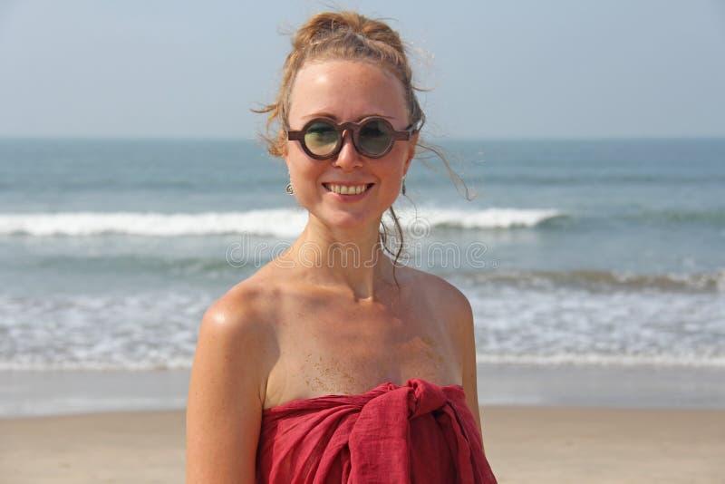 Piękna dziewczyny pokraka w czerwonym blondynie na tle morze i sukni, Lato dziewczyna w round drewnianych szkłach niezwykły fotografia stock