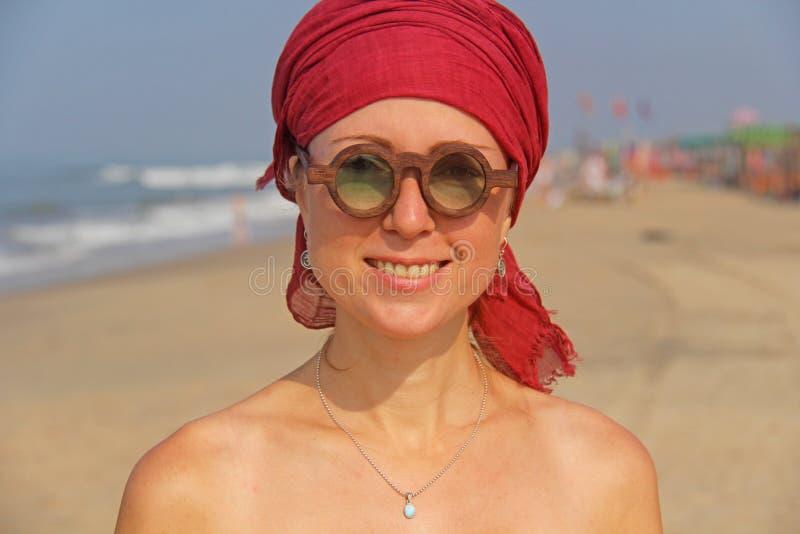 Piękna dziewczyny pokraka z czerwonym armband na jej głowie na tle morze, Lato dziewczyna w round drewnianych szkłach niezwykły fotografia stock