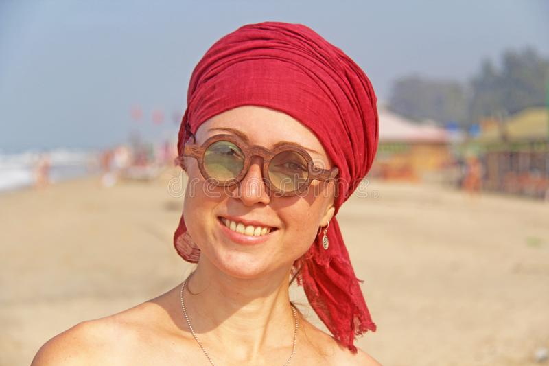 Piękna dziewczyny pokraka z czerwonym armband na jej głowie na tle morze, Lato dziewczyna w round drewnianych szkłach niezwykły zdjęcia royalty free
