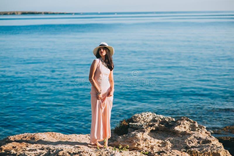 Piękna dziewczyny pozycja na skalistym wychodu nadmorski zdjęcie stock