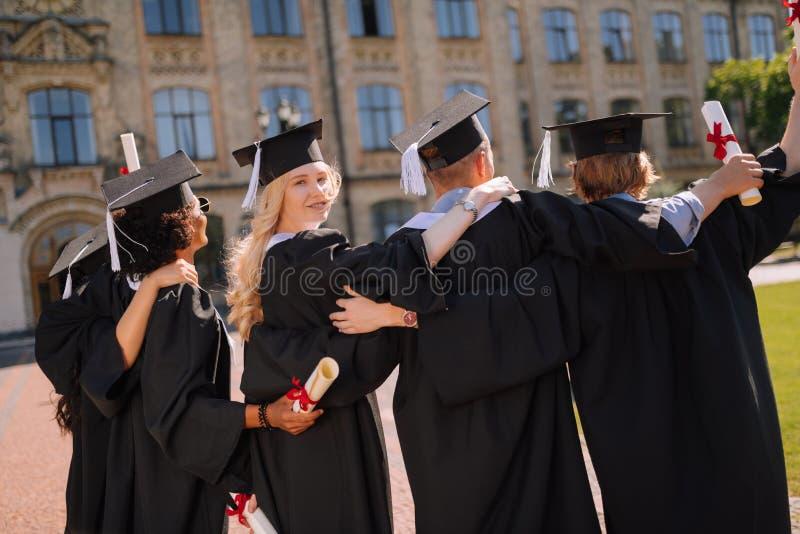 Piękna dziewczyny pozycja z jej przyjaciółmi przed uniwersytetem fotografia royalty free