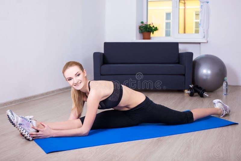 Piękna elastyczna kobieta robi rozciągania ćwiczeniu na joga macie a zdjęcia stock