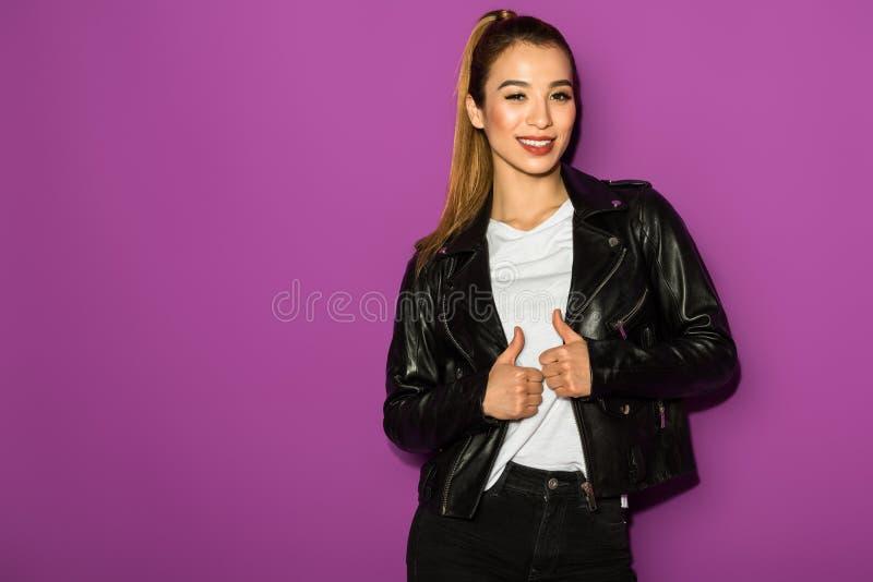 piękna elegancka azjatykcia dziewczyna ono uśmiecha się przy kamerą w skórzanej kurtce zdjęcie royalty free
