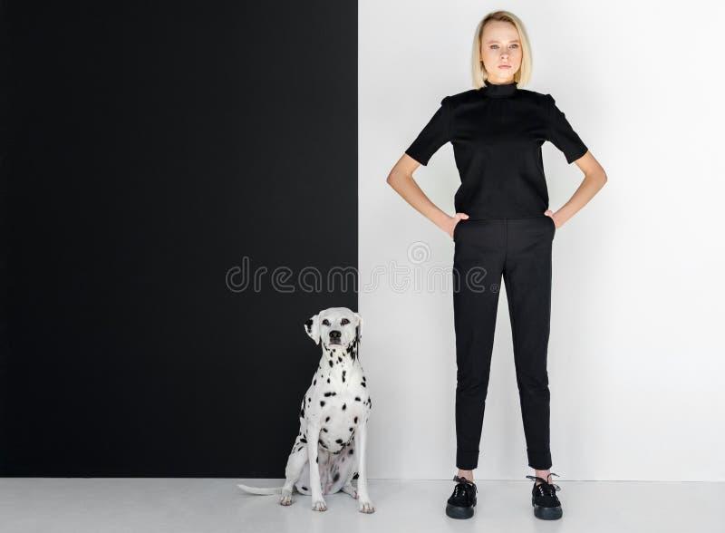 piękna elegancka blondynki kobieta stoi blisko czarny i biały ściany w czerni ubraniach zdjęcie stock