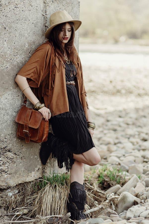 Piękna elegancka boho kobieta z kapeluszem, rzemienna torba, krana ponch fotografia royalty free