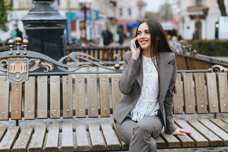 Piękna elegancka dziewczyna opowiada na telefonie na ulicach obraz royalty free