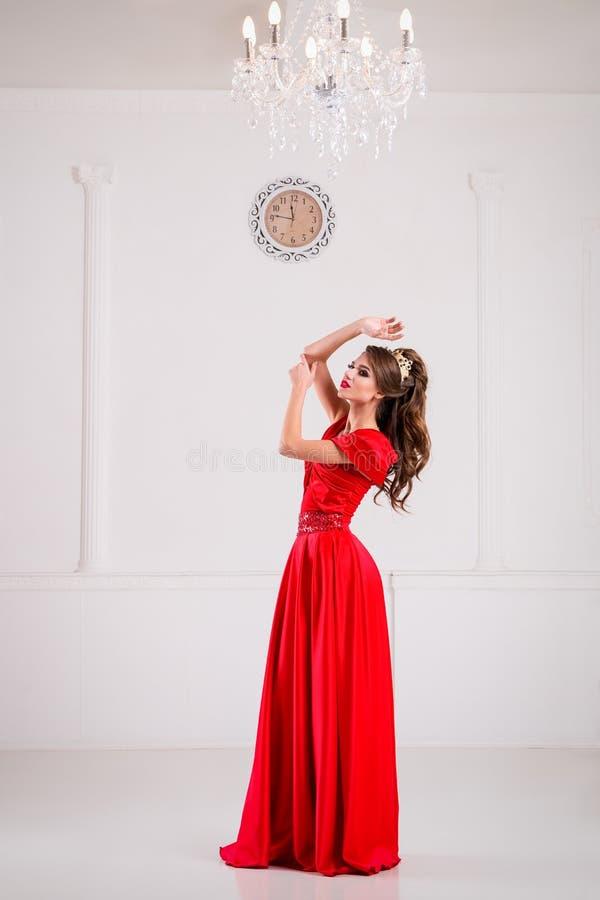Piękna elegancka dziewczyna w długiej czerwieni sukni, butach i stoi fotografia royalty free