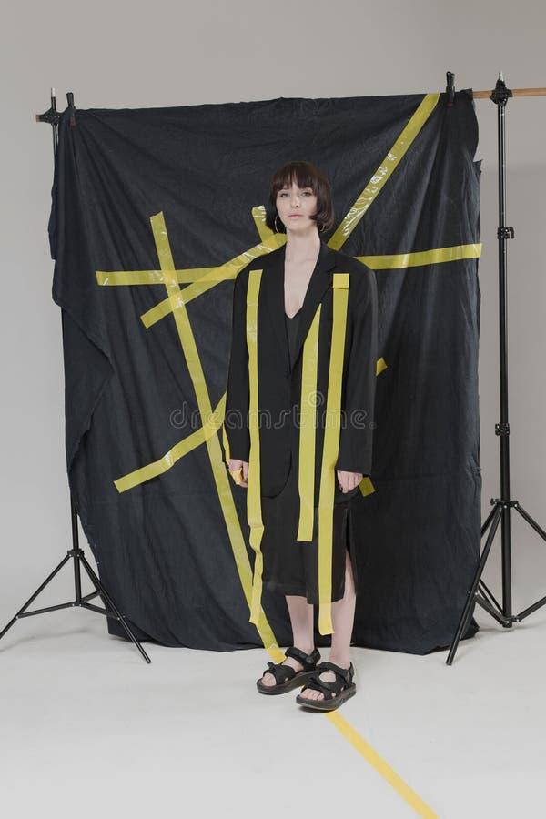 Piękna, elegancka dziewczyna w modnych czerni ubraniach z krótkim czarni włosy, Modny studio strzał obraz stock