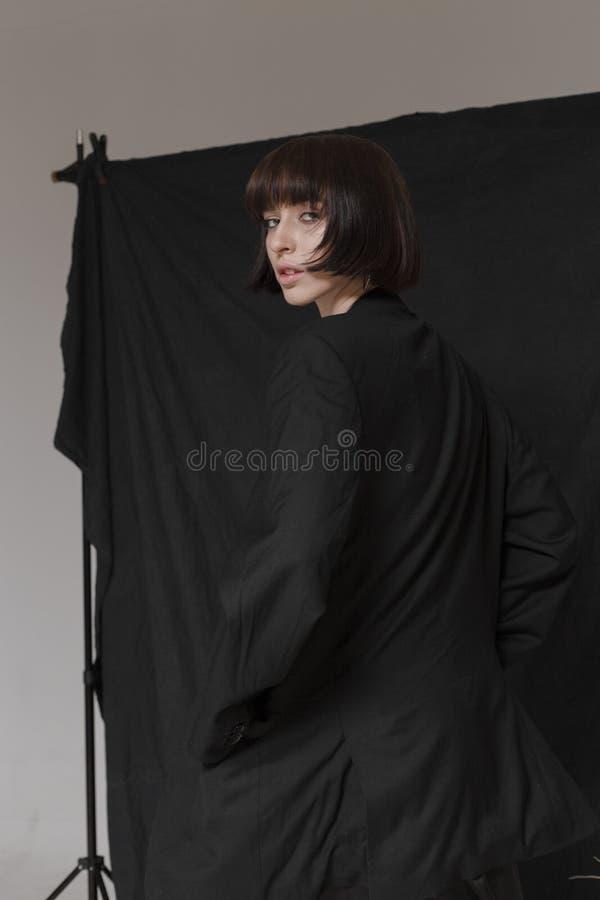 Piękna, elegancka dziewczyna w modnych czerni ubraniach z krótkim czarni włosy, Modny studio strzał obrazy stock