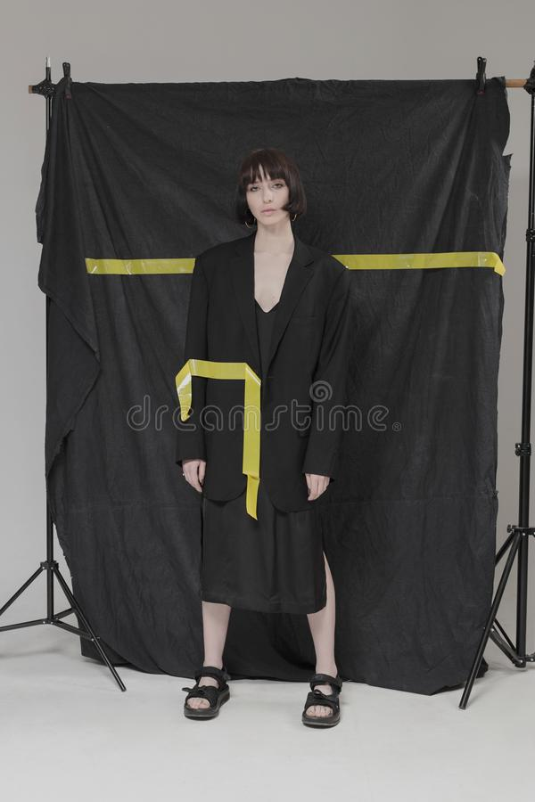 Piękna, elegancka dziewczyna w modnych czerni ubraniach z krótkim czarni włosy, Modny studio strzał fotografia royalty free