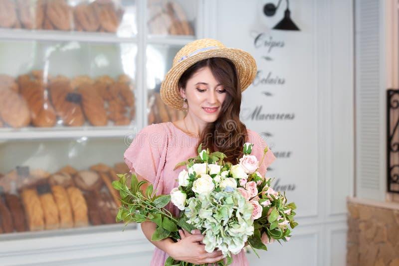 Piękna elegancka dziewczyna w rocznika smokingowym i słomianym kapeluszu we wnętrzu Francuskiej piekarni Rozochocona dziewczyna z zdjęcie stock